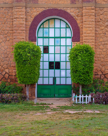 Closed grunge door with green metal grid framed by two green bushes in orange colored bricks stone wall in sunrise time at Montaza public park, Alexandria, Egypt Stock Photo