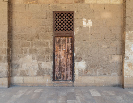 Facade of old abandoned stone bricks wall with one weathered wooden door and wooden grid window, Old Cairo, Egypt Stock Photo