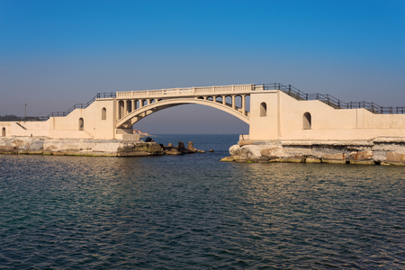 Bridge in the sea at Montazah park with calm sea and clear sky at sunrise time, Alexandria, Egypt Stock Photo