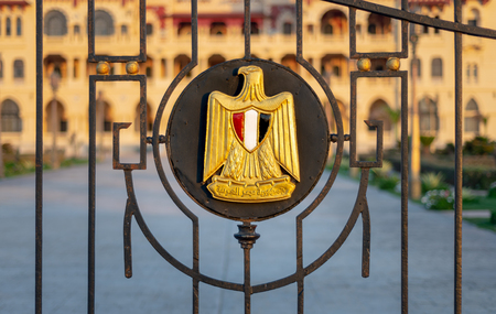 Logo of Egypt on an iron fence revealing Montaza Presidential Palace, consists of Golden Eagle of Saladin holding a scroll with Arabic text (Arab Republic of Egypt) and a shield with the flags colors