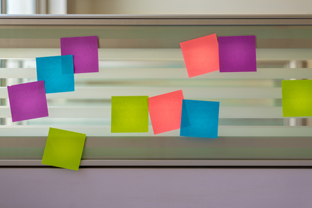 Randomly scattered colored sticky notes over glass screen of a bench desk