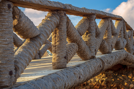 Wooden fence made of palm trunks with partly cloudy sky in sunrise time at Montaza public park in summer time, Alexandria, Egypt Stock Photo
