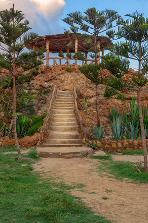 Natural stone stairway with green bushes on both sides leading to wooden pergola with partly cloudy sky at Montaza Park in summer time, Alexandria, Egypt Stock Photo