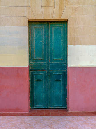 Old grunge green wooden door in an old wall painted in beige and red, Montaza Public Park, Alexandria, Egypt Stock Photo