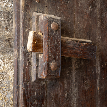 Angled view closeup of a wooden aged latch over a wooden opened door Stock Photo - 105519516