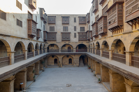 Facade of caravansary (Wikala) of Bazaraa, with vaulted arcades and windows covered by interleaved wooden grids (mashrabiyya), suited in Tombakshia street, Al Gamalia district, Medieval Cairo, Egypt Editorial