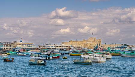 Alexandria, Egypt - December 3 2015: Old east harbor of Alexandria city at the Mediterranean Sea with fishing boats in the foreground and the Citadel of Qaitbay in the background in cloudy winter day Editorial