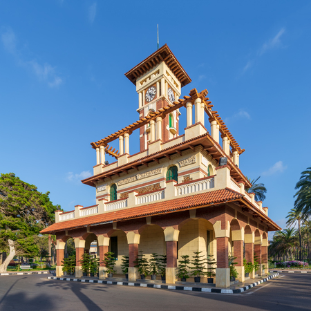The clock tower in Montaza public park with decorated stone wall, green wooden window shutters, and red tile canopies, Alexandria, Egypt Stock Photo