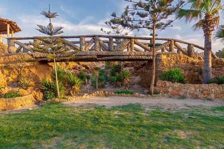 Wooden bridge made of palm trunks over a cavity full of bushes at Montaza park in summer time, Alexandria, Egypt Stock Photo - 105519523