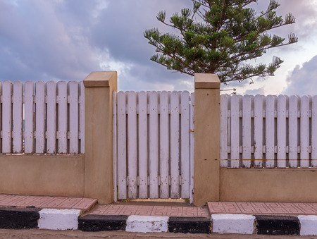 White weathered wooden garden gate and fence with background of single tree and cloudy sky at Montaza public park, Alexandria, Egypt Stock Photo
