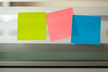 Three colored sticky notes over glass screen of a bench desk
