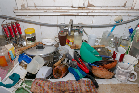 Pile of dirty utensils in a kitchen washbasin