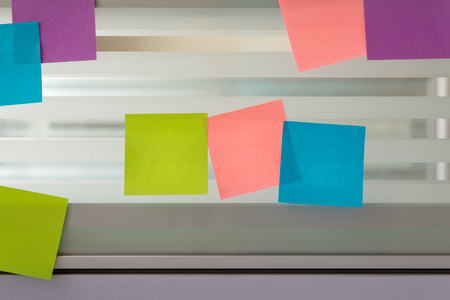 Three colored sticky notes surrounded by randomly scattered sticky notes over glass screen of a bench desk Stock Photo