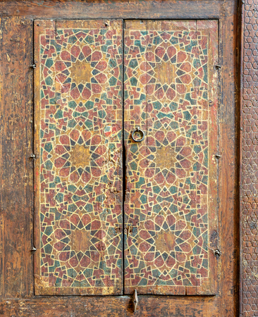 Ornaments of a wooden cupboard painted with colored geometrical patterns embedded in the walls of Sultan al Ghuri Mausoleum, Cairo, Egypt Stock Photo