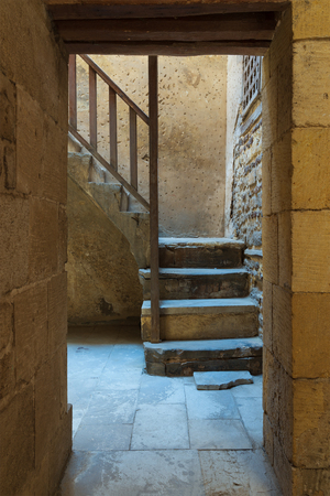 Ancient external old bricks stone wall and doorway revealing a stone staircase with wooden balustrade, Old Cairo, Egypt
