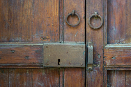 Closeup of a wooden aged latch and two rusted ring door knockers over an ornate wooden door, Cairo, Egypt