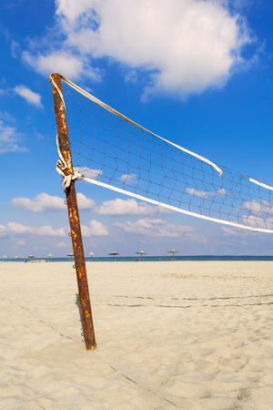 Torn volleyball net on the beach with cloudy blue sky and yellow sand in the morning Stock Photo