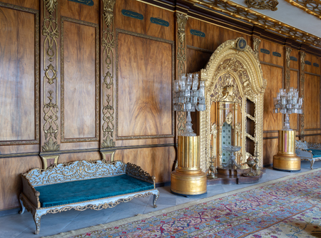 Manial Palace of Prince Mohammed Ali Tawfik. Residence of princes mother with golden ornate niche, blue couch and ornate wooden wall, Cairo, Egypt