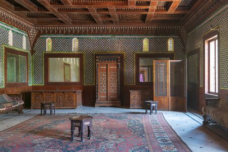 Manial Palace of Prince Mohammed Ali. Moroccan hall at the ceremonies building with blue Turkish floral pattern ceramic tiles, vintage furniture, and framed mirrors, Cairo, Egypt Stock Photo - 133071035