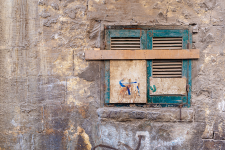 Old grunge window with closed green broken shutters on dirty cracked bricks stone wall Stock Photo - 108923650