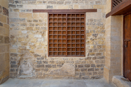 Mamluk era wooden closed window with wooden ornate grid over stone bricks wall Editorial
