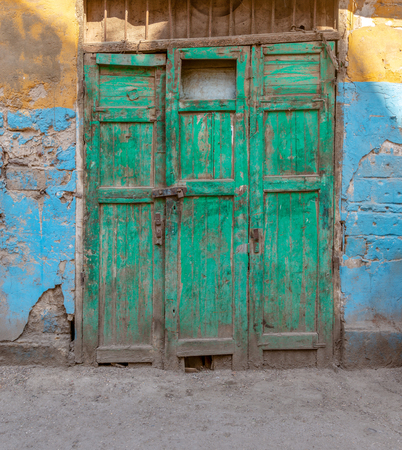 Closed green wooden grunge weathered abandoned door on dirty wall painted in yellow and blue colors