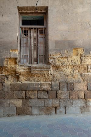 Broken windows and grunge stone bricks wall in abandoned Darb El Labana district, Cairo, Egypt Stock Photo - 127284395