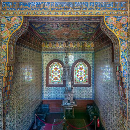 Cairo, Egypt - August 26 2018: Wooden staircase, Turkish ceramic tiles wall, ornate ceiling and stained glass windows, Residence hall at Manial Palace of Prince Mohammed Ali Stock Photo - 133071073