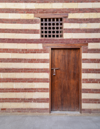 Background of old wall with red bricks and yellow stones, wooden closed door and window, Cairo, Egypt Stock Photo - 127285068