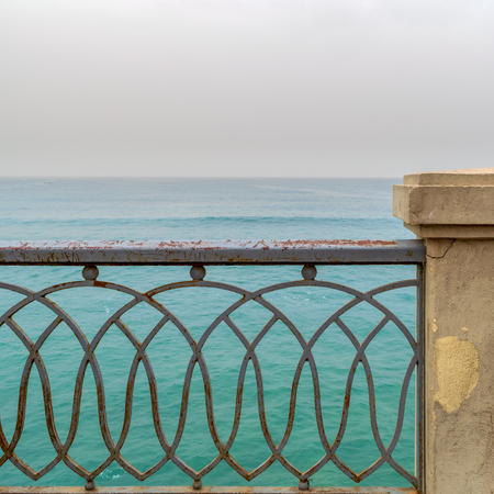 Rusted metal decorated protective fence of Stanley bridge at Alexandria, Egypt with Mediterranean Sea in the background Stock Photo - 127286694