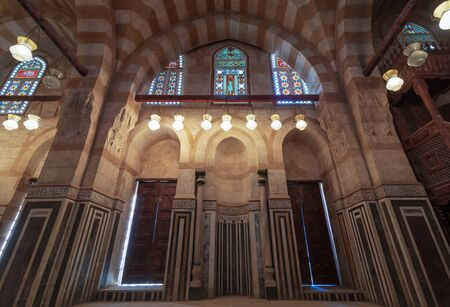 Marble wall with mihrab (Embedded niche), two wooden doors, huge arches and stained glass windows at mosque attached to Khayer Bek Mausoleum, Darb Al-Ahmar district, Old Cairo, Egypt Stock Photo - 133071419