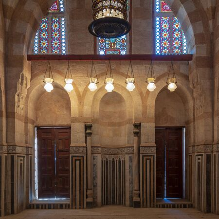 Marble wall with mihrab (niche), two wooden doors, huge arches and stained glass windows at mosque attached to Khayer Bek Mausoleum, Darb Al-Ahmar district, Old Cairo, Egypt Stock Photo - 133071453