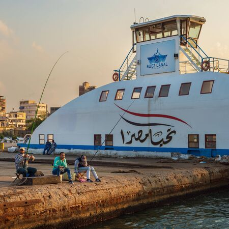 Port Fuad, Egypt - November 10, 2018: Local citizens of Port Fuad district fishing beside Port Said ferry boat at Suez Canal Stock Photo - 133071534