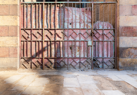 Background of old weathered grunge antique wrought iron gate with geometrical pattern ornaments and sone bricks wall Stock Photo - 127683928