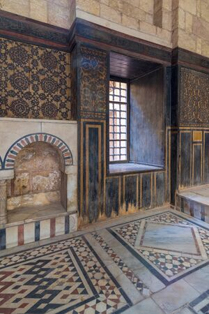 Wooden wall decorated with painted floral patterns, embedded arched niche and marble floor decorated with geometric patterns at ottoman era historic house of Moustafa Gaafar Al Seleehdar, Cairo, Egypt Stock Photo - 133071828