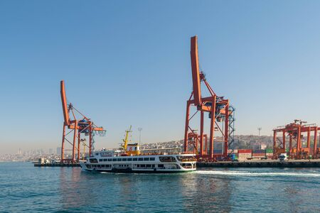 Day shot of the cranes in the shipyard of the Port of Haydarpasha, and passing ferry boat with city view in the background, Istanbul, Turkey Stock Photo - 133071924
