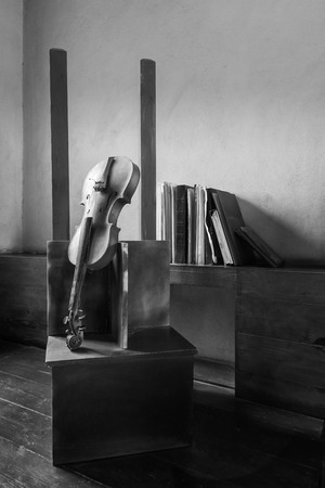 Black and white still life shot of broken old broken violin and vintage grunge books Stock Photo - 127702286