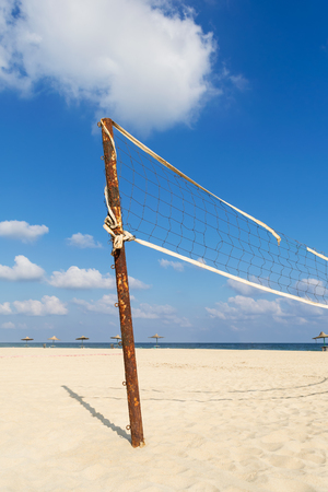Torn volleyball net on the beach with cloudy blue sky and yellow sand in the morning Stock Photo - 127441238