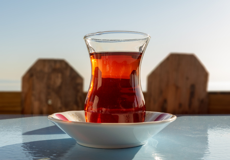 Glass of traditional Turkish tea, with background of wooden fence and sky, Istanbul, Turkey Stock Photo - 127441343