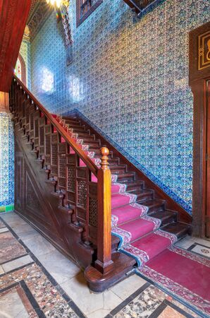 Wooden staircase with ornate red carpet, decorated wooden balustrade and Turkish ceramic tiles wall at the Residence hall, Manial Palace of Prince Mohammed Ali, Cairo, Egypt Stock Photo - 133072287