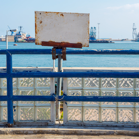 White blank grunge rusted sign attached to blue old metal fence revealing Suez Canal, Port Said, Egypt Stock Photo - 127441347