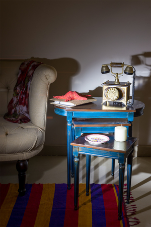 Interior shot of old golden telephone set, white candle, red starfish and colorful ornate plate over three nested tables with blue legs over off white wall, and cream armchair with harsh light Stock Photo - 127441478
