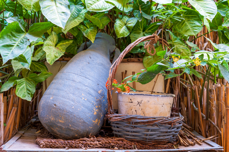 Blue pottery container and wicker basket on background of wooden cage, green leaves and assembled reeds Stock Photo - 127441485