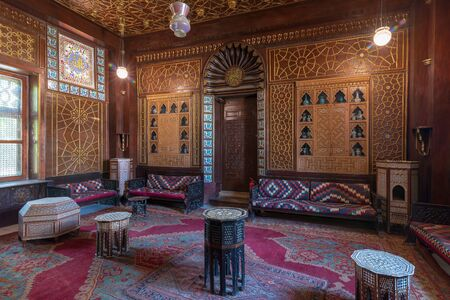 Manial Palace of Prince Mohammed Ali. Guests Hall with wooden ornate ceiling, wooden ornate door, lanterns, colorful ornate couches, tea tables and ornate carpet, Cairo, Egypt Stock Photo - 133072754