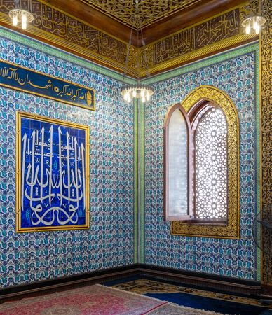 Turkish blue floral pattern ceramic tiles wall with wooden arched decorated window and moral with Arabic calligraphy at the public mosque of Manial Palace of Prince Mohammed Ali, Cairo, Egypt Stock Photo - 133072755