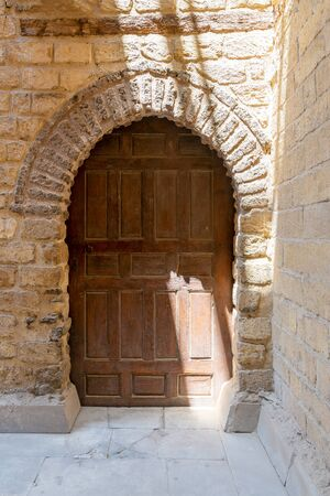 Vaulted closed wooden grunge door in bricks stone wall, Old Cairo, Egypt Stock Photo - 127702332
