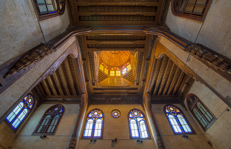 Wooden decorated dome mediating ornate ceiling with floral pattern decorations and stained glass windows at Sultan al Ghuri Mausoleum, Cairo, Egypt Stock Photo - 127298923