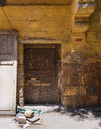 Broken wooden brown door on grunge stone bricks wall painted in orange in abandoned Darb El Labana district, Cairo, Egypt Stock Photo - 131870174