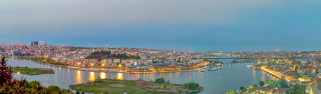 Istanbul city view from Pierre Loti Teleferik station overlooking Golden Horn with Halic Bridge, Golden Horn Metro Bridge and historical mosques at sunset, Eyup District, Istanbul, Turkey Stock Photo - 127298925