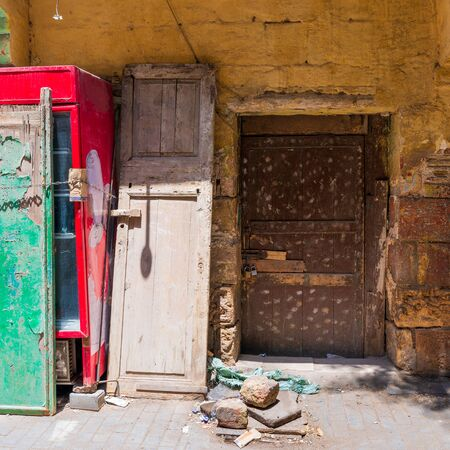 Broken wooden brown door on grunge stone bricks wall painted in orange in abandoned Darb El Labana district, Cairo, Egypt Stock Photo - 131871484
